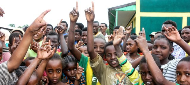A large group of children at Chicho School waving